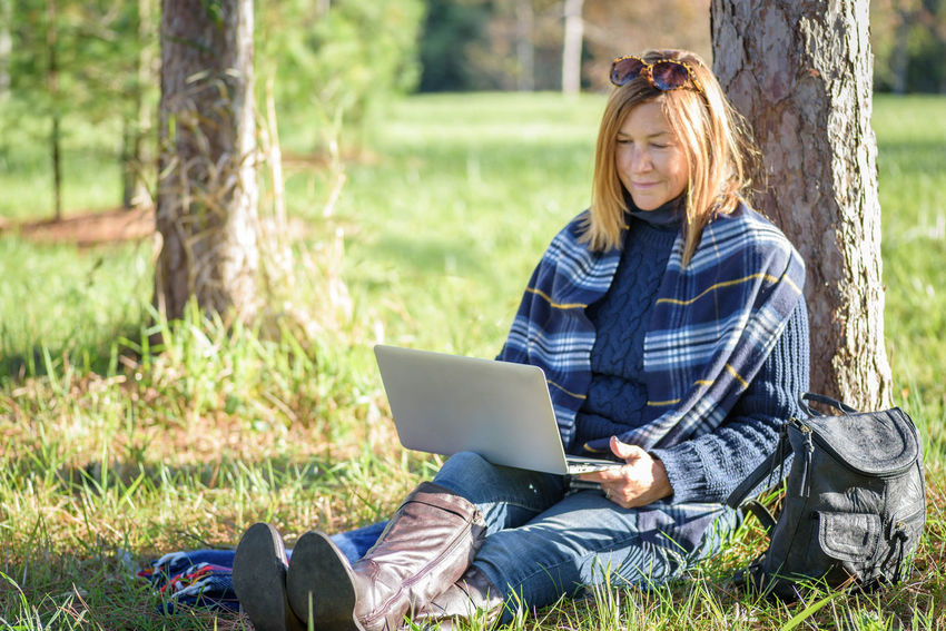 woman sitting in park in grass by tree working on laptop computer in autumn Boots Campus Grass Happy Lifestyle Nature Sitting Trees Woman Working Class Degree Getting Away From It All Grassy Ground Laptop One Person Online  Outdoors Park Park - Man Made Space Scarf Studying Style Wireless Technology