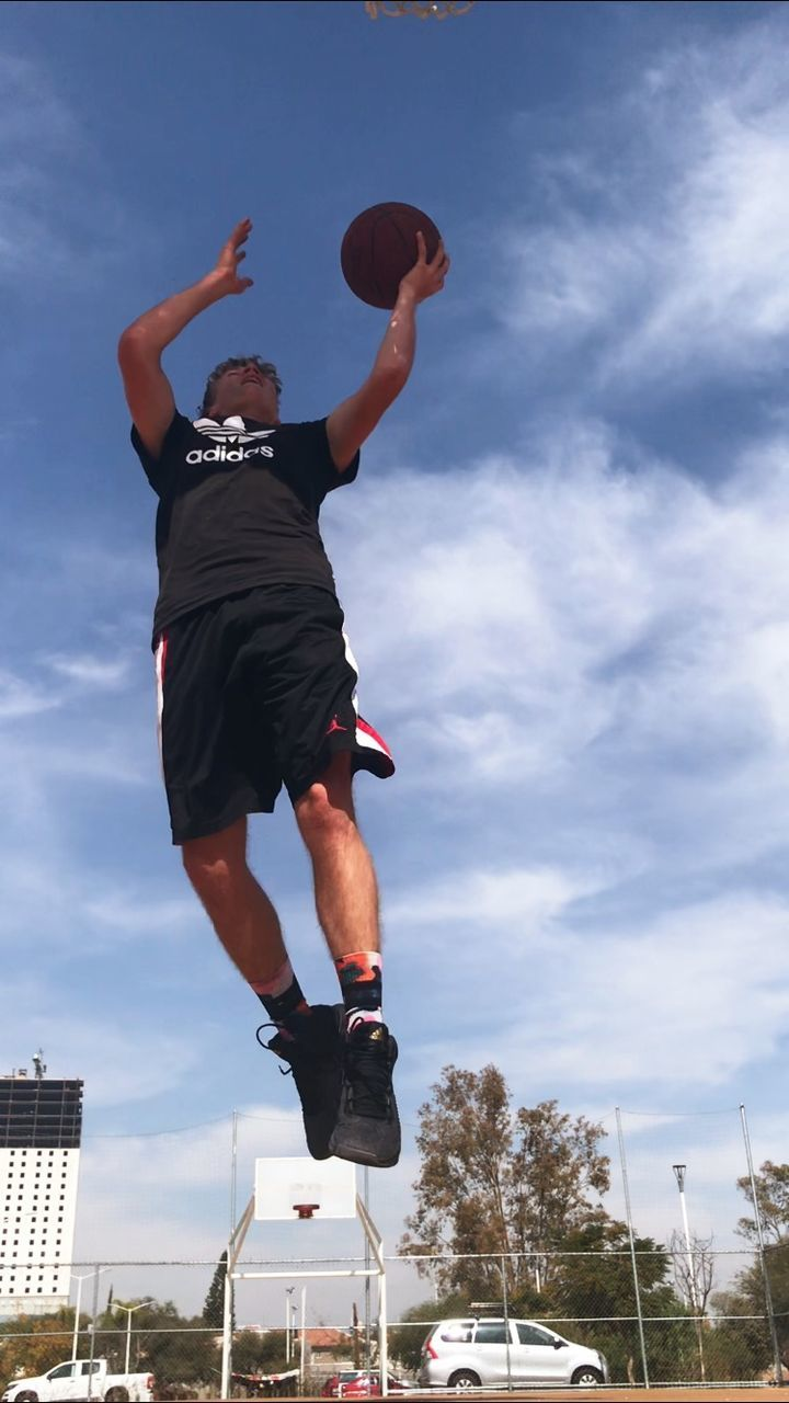 sky, jumping, one person, low angle view, cloud - sky, motion, mid-air, real people, leisure activity, nature, men, vitality, human arm, day, full length, lifestyles, architecture, arms raised, sport, outdoors, effort
