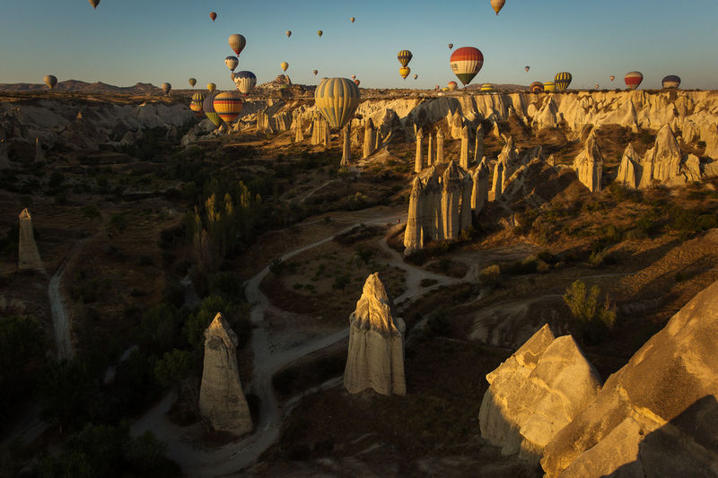 Hot air balloons flying over rocky landscape during sunny day