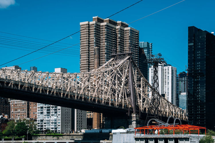 New York City - USA - May 15 2019: Queensboro bridge and apartment buildings of Manhattan midtown from Roosevelt Island East River Landscape America Architecture Blue Bridge Building Cable City Cityscape Day Downtown East Famous Garden Island Landmark Lifestyle Manhattan Midtown Modern New New York City NY NYC Panoramic Park Queensboro River Roosevelt Roosevelt Island Scenic Sky Skyline Skyscraper Spring Street Sunny Tourism Tower Tram Tramway Transportation Travel Urban USA View Water Waterfront York