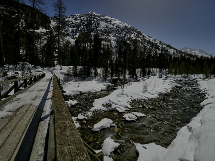Wooden bridge by a snowy creek in the moonlight Cold Temperature Snow Winter Beauty In Nature Scenics - Nature Tranquil Scene Tranquility Mountain No People Nature White Color Sky Non-urban Scene Tree Plant Covering Direction Mountain Range Outdoors Snowcapped Mountain Long Bridge Creek Val Roseg Place To Be