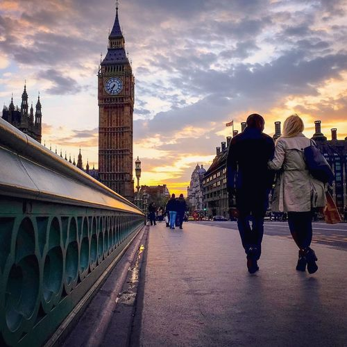 Rear view of couple walking on westminster bridge by big ben against sky during sunset