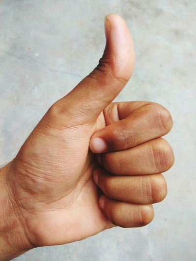 Close-up of hand gesturing thumbs up against wall