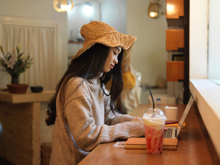 Young woman working on laptop by milkshake at cafe