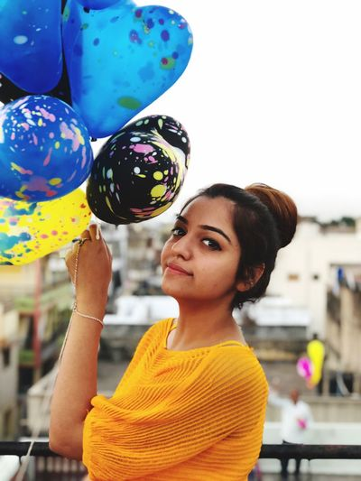 Portrait of young woman holding helium balloons in city
