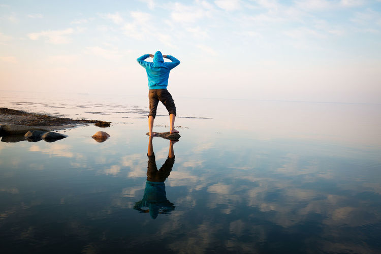 Rear view of man standing on shore with reflection against sky
