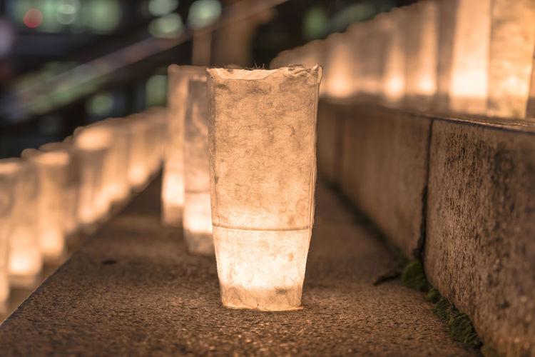 Close-up of illuminated lamp on wall at night