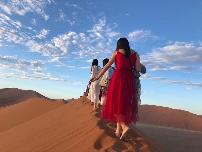 Rear view of women on desert against sky