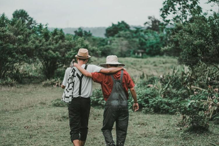 Rear view of friends walking on street amidst trees