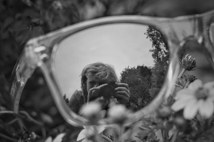 Reflection of woman photographing through camera in sunglasses on grass