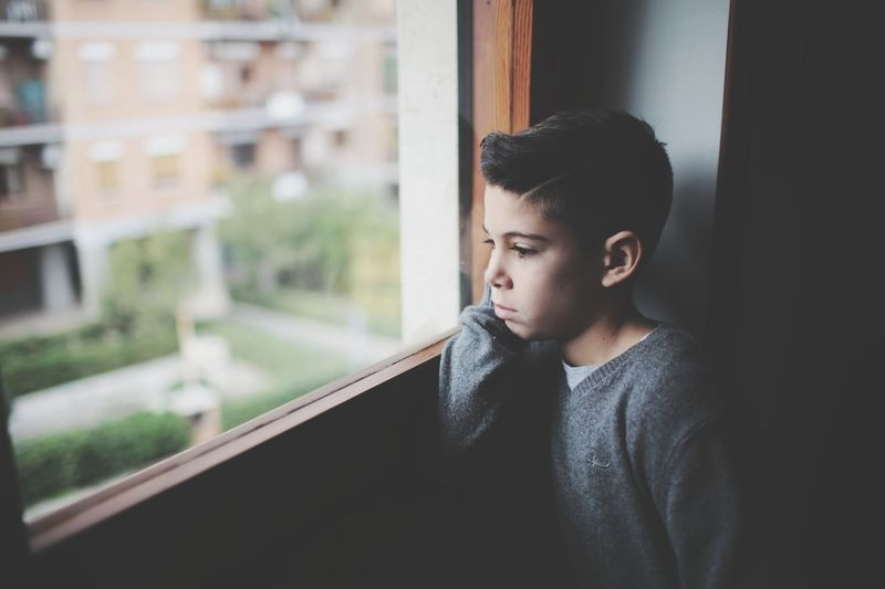 Close-Up Of Boy Looking Through Window At Home