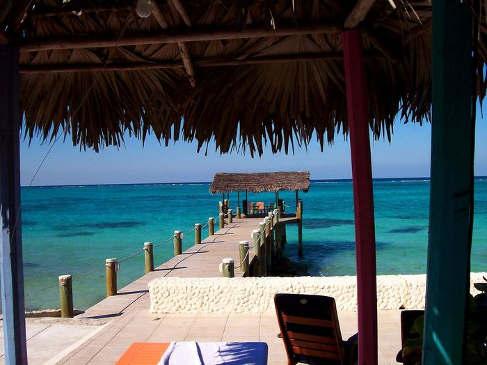 A view of the ocean and a tiki hut from under a tiki hut Beach Beauty In Nature Blue Caribbean Colorful Day Horizon Over Water Margaritaville No People Outdoors Peaceful Resort Scenic View Scenics Sea Sky Sunlight Tiki Tikiş Tranquility Tropical Paradise Tropical Vacation Resort Tropics Vacation Water