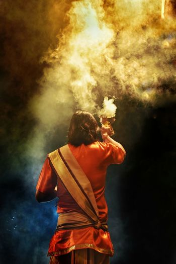 Rear view of woman holding container emitting smoke