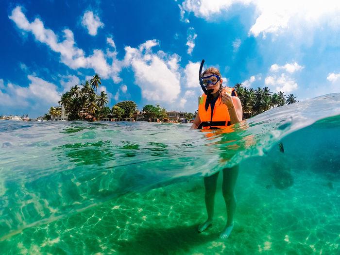 Portrait of woman in sea against sky . dom gopro case . underwater in srilanka