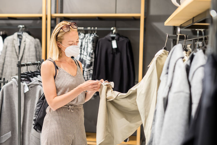 Woman wearing mask standing in clothing store