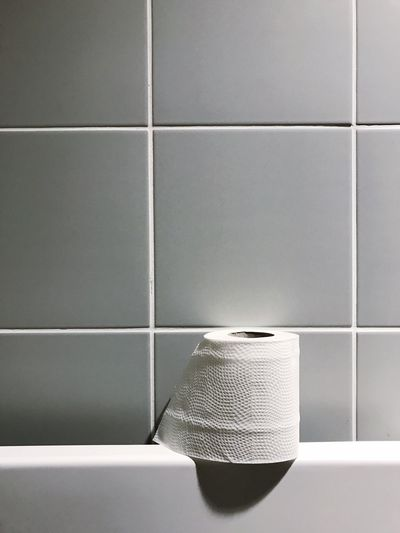 Close-up of toilet paper against wall
