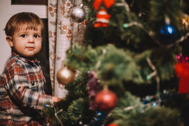 Portrait of cute boy standing by christmas tree at home