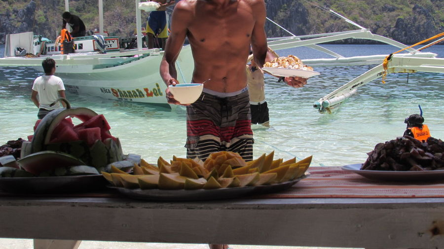 Serving food People Water Adult Food Outdoors Day Nautical Vessel Adults Only Adventure Real People Miles Away Beauty In Nature Beach Sand Relaxation Vacations Human Body Part One Person Travel