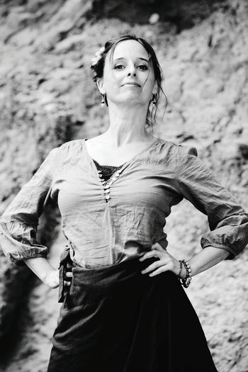 Portrait Of Woman With Hand On Hip Standing Against Rock