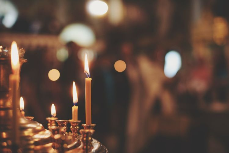 Close-Up Of Lit Candles In Church