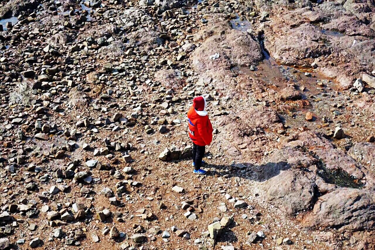 rock - object, red, full length, real people, one person, leisure activity, adventure, day, outdoors, hiking, rear view, lifestyles, standing, climbing, nature, beauty in nature, people