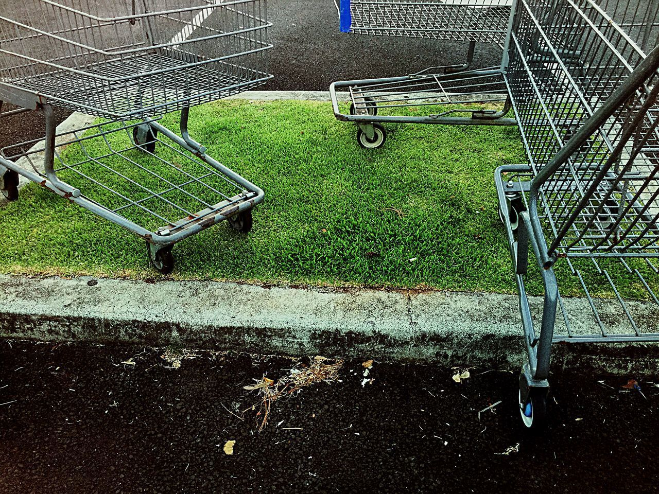 shopping cart, absence, trolley, grass, metal, no people, day, empty, green color, seat, shopping, plant, abandoned, transportation, consumerism, nature, outdoors, bench, high angle view, field, park bench, wheel