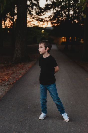 Boy looking away while standing on road during sunset