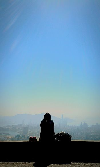 Rear view of silhouette man photographing woman against clear blue sky