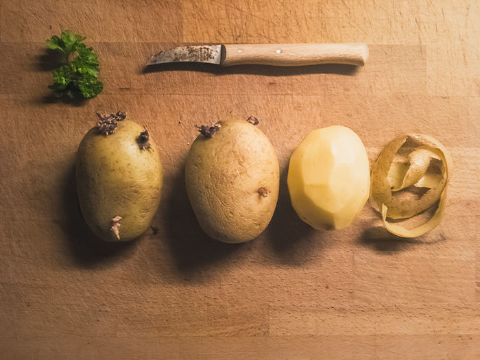 High angle view of raw potatoes on wooden table