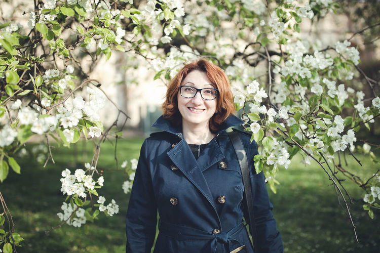 Confident middle aged armenian woman in a blue trench coat and glasses under the blooming tree