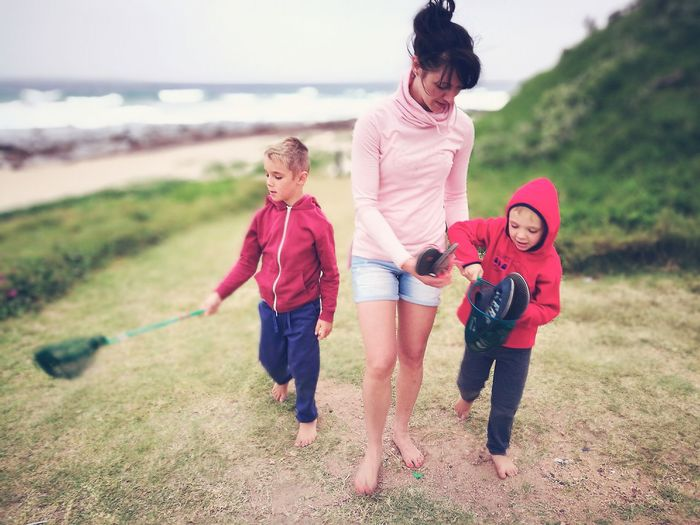 Family walking on the beach Child Females Family Fun Happiness Joy Outdoors Adult People Day Nature Holiday Beach Fishing Net Ocean Rocks Windy Summer Sand Hoody Three People