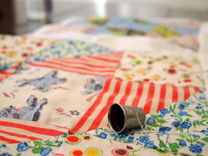 Metal drinking glass on multi colored bed sheet at home