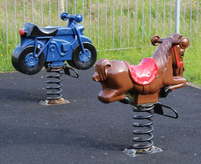 Blue Motorcycle. Brown Horse. Child. Childrens Playground Rides. Day Empty... Leisure Activity No People. Beauty In Nature Diamond Pattern Outdoors Playground. Springs. Two Rides. Two.