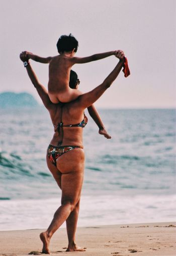 Full length of shirtless man standing on beach