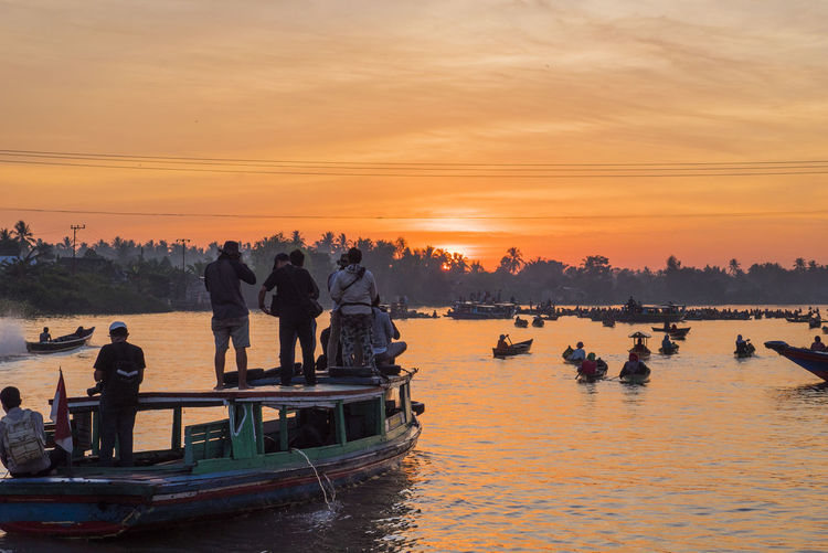 People on boat in river against sky during sunset