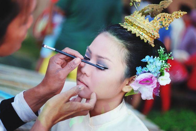 Artist applying eyeshadow on young woman
