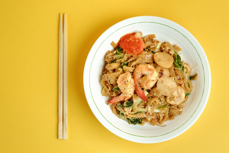 Fried rice flat noodle or char kwoey teoy from Indonesia 10 Chinese Food Indonesian Food Malaysian Food Noodles Shrimp Charkweoyteoy Colored Background Dinner Directly Above Flat Rice Noodles Food Food And Drink Healthy Eating Kwetiaw Ready-to-eat Vegetable Yellow