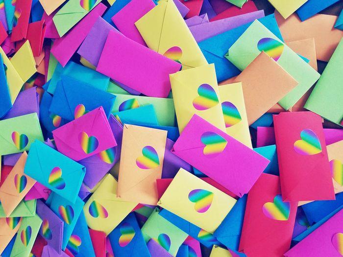Full frame shot of colorful envelopes with heart shape