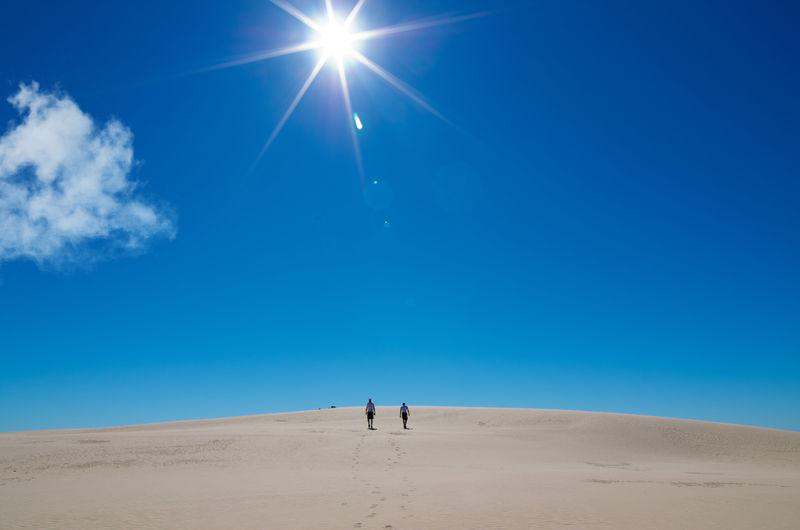 Man walking on sand dune against blue sky