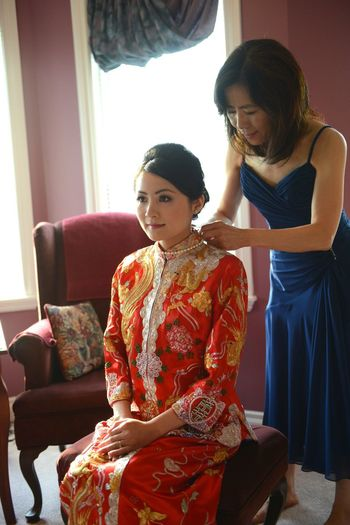 Weddings Around The World Canadian Chinese Wedding the bride is wearing a Chinese Tranditional Wedding Gown getting ready to the groom coming. And the mom is putting on the necklace for her daughter means pass the blessings n good luck.@ YYC