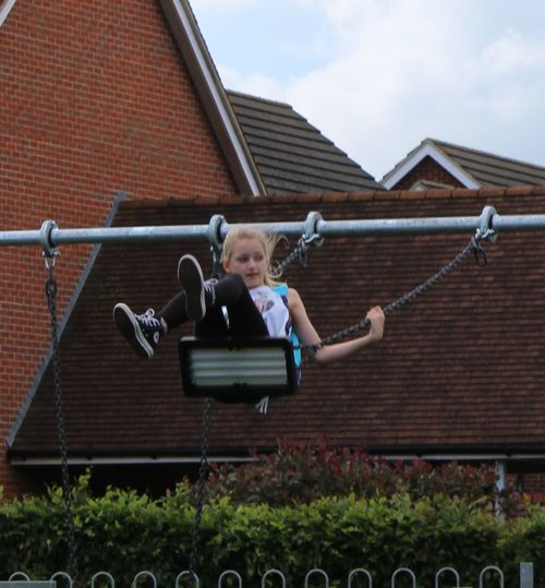 Architecture Casual Clothing Day Fun Girl On A Swing. Child. Leisure Activity Outdoors Play.n. Playground. Sky Swing...
