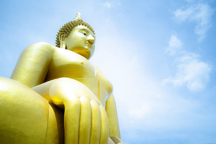 Low angle view of statue of buddha against sky