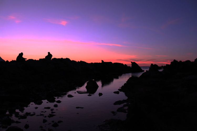 Silhouette rocks on shore against sky during sunset