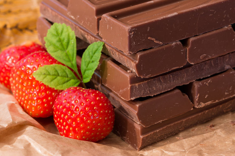 Close-up of strawberries by chocolate bars on table