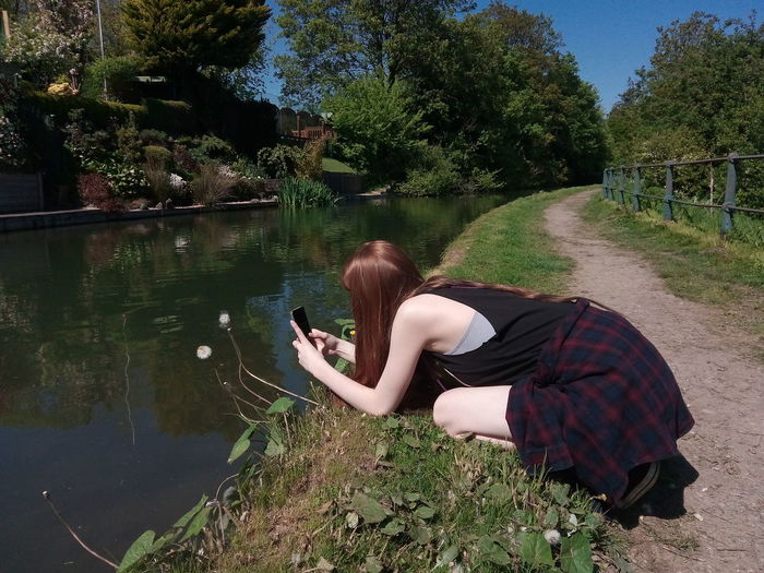 The rare glimpse of the species known as the teenager! Riverpath Water Reflections Reflections Calm Water Trees Greenery Photographer Teenager Young Lady Taking Photos River Riverside Riverview Nature Beauty In Nature Blue Sky Tree Wireless Technology Technology Photography Themes Water Photographing Women Mobile Phone Plant Life Leisure