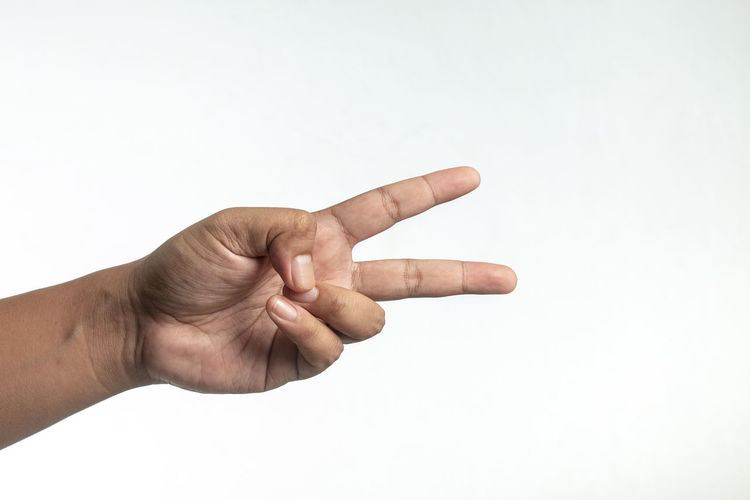 Low angle view of human hand against white background