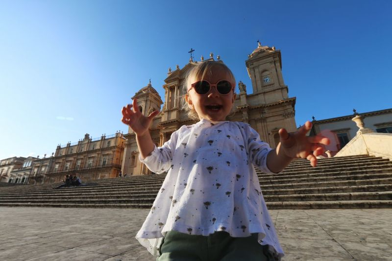 Low Angle View Of Cute Baby Girl Wearing Sunglasses While Standing Against Church