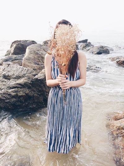 Woman Covering Face By Flowers At Beach Against Sky