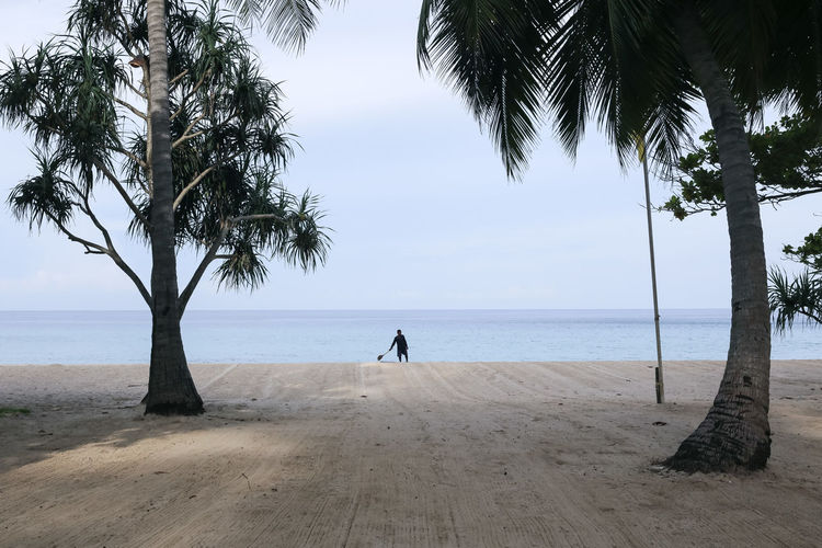 Surin beach, Phuket, Thailand Beach Beach Cleaning Brooming Cleaner Horizon Over Water Outdoors Real People Sand Sea Sisyphus Sky Surin Surin Beach The Great Outdoors - 2017 EyeEm Awards Tree