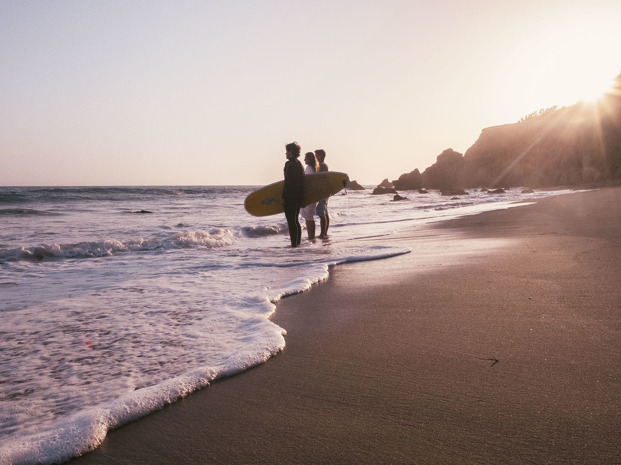 sea, beach, real people, nature, shore, sunset, scenics, water, beauty in nature, full length, lifestyles, leisure activity, outdoors, men, sand, vacations, walking, wave, clear sky, sky, silhouette, standing, horizon over water, day, young adult, people